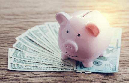piggy bank on top of dollar bills